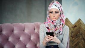 De mooie moslimvrouw met heldere kleurrijke hijab, zit op roze bank stock video