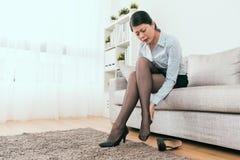 De mooie onderneemster voelt de klem van de beenhiel stock foto