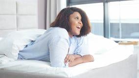 De mooie ontzagwekkende vrouw heeft blije uitdrukking, ligt op maag in bed stock footage