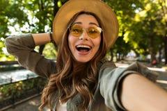 De mooie opgewekte geschokte vrouw neemt in openlucht een selfie door camera royalty-vrije stock foto