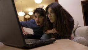 De mooie opgewekte jonge paar het letten op video's van de wittebroodsweken exotische bestemming op laptop in de woonkamer stock video