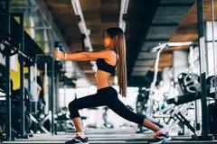 De mooie opheffende domoren van de geschiktheidsvrouw Geschiktheids sportief meisje die in gymnastiek uitoefenen Royalty-vrije Stock Foto