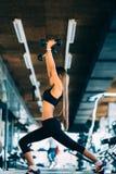 De mooie opheffende domoren van de geschiktheidsvrouw Geschiktheids sportief meisje die in gymnastiek uitoefenen Royalty-vrije Stock Foto's
