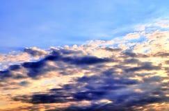De mooie oranje vormingen van de zonsondergangwolk met zonlicht die door glanzen stock foto
