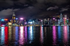 De mooie panoramascène van de stad van Hongkong uit het stadscentrum bij nacht met wolkenkrabbers verlichtte het nadenken in de r stock foto's