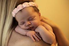De mooie pasgeboren slaap van het babymeisje op de schouders van het mamma Royalty-vrije Stock Foto's