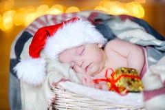 De mooie peuter in een Santa Claus-hoed houdt een gifthand en slaap in een mand Royalty-vrije Stock Afbeeldingen