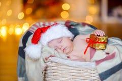 De mooie peuter in een Santa Claus-hoed houdt een gifthand en slaap in een mand Stock Afbeelding