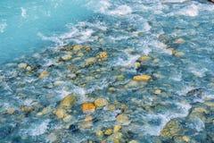 De mooie rimpelingen op rivier stromen over kleurrijke stenen in de zomerzonneschijn, Siberië, Altai-Republiek royalty-vrije stock afbeelding