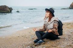 De mooie roodharige vrouw in een hoed en een sjaal met een rugzak zit in een meditatieve positie inzake de kust tegen stock afbeeldingen