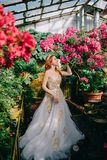 De mooie roodharige vrouw inhaleert geur van bloeiende bloemen royalty-vrije stock afbeelding