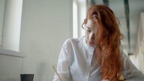 De mooie roodharigevrouw werkt, het trekken, zittend bij lijst in bureaubinnenland stock video