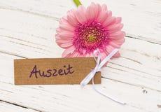 De mooie roze bloem van het gerberamadeliefje met etiket en Duits woord, Auszeit, betekent onderbreking royalty-vrije stock foto