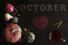 De mooie rustieke dalingsvlakte legt met bladeren, pompoenen, kastanjes, kop thee en brieven oktober op houten achtergrond stock afbeeldingen
