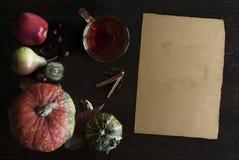 De mooie rustieke dalingsvlakte legt met glas van thee, bladeren, pompoenen, kastanjes, kop thee en oude document rol, op houten  royalty-vrije stock afbeelding