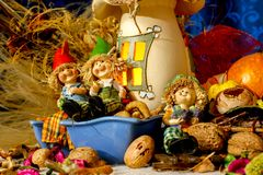 De mooie samenstellings iwith beeldjes van kind, snacks, drogen bladeren, okkernoten en rustieke decoratie royalty-vrije stock fotografie