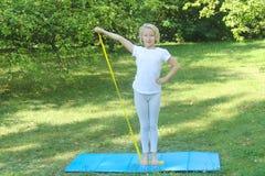 De mooie school verouderde jong geitjemeisje het spelen sporten met een elastiekje en een mat in openlucht in het park Stock Fotografie