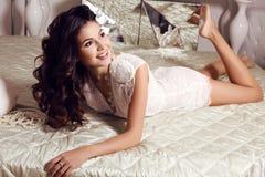 De mooie sensuele vrouw met lang donker haar draagt elegant kantkostuum Stock Fotografie