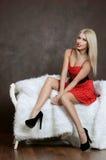 De mooie sensuele vrouw zit op stoel Stock Fotografie