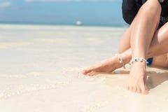 De mooie sexy benen van vrouwen op het strand Het concept van de strandreis Stock Foto's