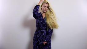 De mooie sexy blondevrouw in donkerblauwe lange kleding stelt tegen studioachtergrond Langzame Motielengte stock footage