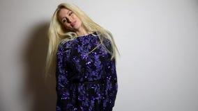 De mooie sexy blondevrouw in donkerblauwe lange kleding stelt tegen studioachtergrond Langzame Motielengte stock video