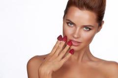De mooie sexy donkerbruine vrouw die vier bessen op haar vingers houden, het sexy glimlachen en gaat frambozen op een witte backg Stock Foto's