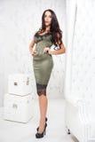 De mooie sexy donkerbruine vrouw met lang haar en de rode lippen in olijfzijde kleden zich op hoge hielen Stock Foto's