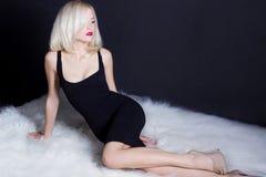 De mooie sexy elegante opvallende blondevrouw met heldere make-up rode lippen in een zwarte kleding ligt op het witte bont in Stu Stock Afbeeldingen