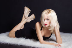 De mooie sexy elegante opvallende blondevrouw met heldere make-up rode lippen in een zwarte kleding ligt op het witte bont in Stu Royalty-vrije Stock Foto's