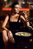 De mooie sexy manier donkerbruine vrouw in duur binnenlands restaurant eet oester en likt één vinger Royalty-vrije Stock Fotografie