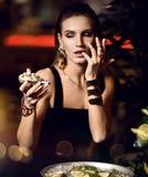 De mooie sexy manier donkerbruine vrouw in duur binnenlands restaurant eet oesterwachten Royalty-vrije Stock Afbeeldingen