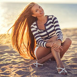 De mooie sexy vrouw is gekleed in een overzees gestript vest zit op de kustdromen Royalty-vrije Stock Foto