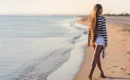 De mooie sexy vrouw is gekleed in een overzees gestript vest zit op de kustdromen Royalty-vrije Stock Foto's