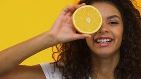 De mooie sinaasappel van de meisjesholding en het knipogen naar camera, die gezonde voeding adviseren stock videobeelden