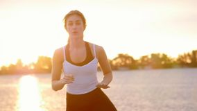 De mooie, slanke jonge blonde vrouw belast met geschiktheid, springt, voert sterkteoefeningen uit Bij dageraad, bij zandig stock videobeelden
