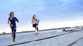 De mooie, slanke jonge vrouwen zijn bezig geweest met geschiktheid, sprong, uitvoeren sterkteoefeningen Bij dageraad, bij de zand stock footage