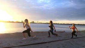 De mooie, slanke jonge vrouwen zijn bezig geweest met geschiktheid, sprong, uitvoeren sterkteoefeningen, duw UPS Bij dageraad, zo stock video