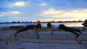 De mooie, slanke jonge vrouwen zijn bezig geweest met geschiktheid, uitvoeren sterkteoefeningen Bij dageraad, langs de zandpijler stock footage
