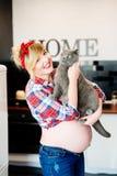 De mooie speld stileerde omhoog jonge zwangere vrouw in keuken stock afbeelding