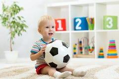 De mooie spelen van de babyjongen met bal stock foto's