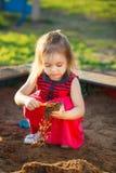 De mooie spelen van de meisjes rode kleding in zandbak kindveiligheid op de speelplaats Royalty-vrije Stock Foto's