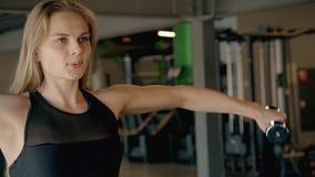 De mooie spiervrouw leidt met sterke gewichtendomoren en sportkleding op stock videobeelden