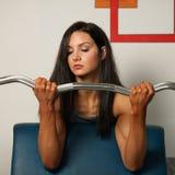 De mooie sportieve vrouw werkt haar wapens in geschiktheidsgymnastiek uit Stock Foto