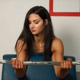 De mooie sportieve vrouw werkt haar wapens in geschiktheidsgymnastiek uit Royalty-vrije Stock Foto's
