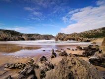 De mooie steenbogen op Playa DE las Cuevas del brengen, Cantabrië in de war Royalty-vrije Stock Foto's