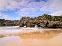 De mooie steenbogen op Playa DE las Cuevas del brengen, Cantabrië in de war Stock Foto