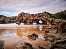 De mooie steenbogen op Playa DE las Cuevas del brengen, Cantabrië in de war Royalty-vrije Stock Afbeeldingen