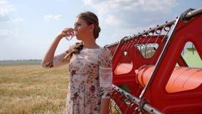 De mooie sterke vrouw drinkt water en onderzoekt afstand op tarwegebied dichtbij maaimachine verzamelt korrel stock footage