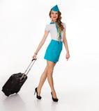 De mooie stewardess houdt bagage Stock Afbeeldingen